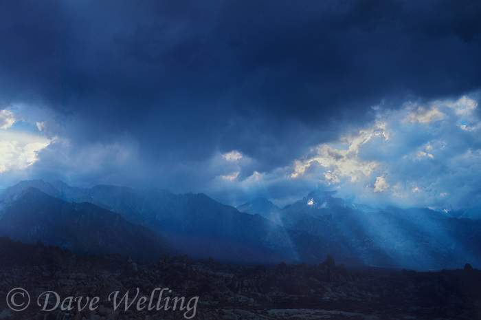 711700289 a clearing summer thunderstorm over the eastern sierras with god rays lighting the alabama hills in the foreground in kern county central california