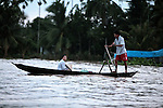 A man paddles a  boat along the Hau River in the Mekong Delta, south of Can Tho, Vietnam. Sept. 30, 2011.