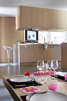 In the contemporary kitchen the cupboards, units and table are all made of oak and a high-tech detail is the television which swivels 360 degrees