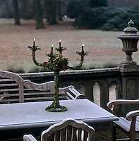 A candelabra decorated with leaves and pine cones stands on a table on the terrace overlooking the park