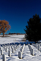 Blue Colorado sky over white snow surrounding white granite headstones at Fort Logan National Cemetery, Denver, Colorado.