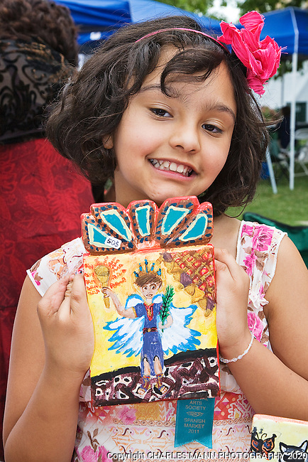 The Santa Fe Spanish Market, held in July, fills the Santa Fe Plaza with artists parton and visitors all celebrating traditional Spanish colonial arts. It is held side by side with the Contemporary Spanish Market which features modern Hispanic artists. Youth artist Simona Rael shows off one of her retablos, a painted wooden tablet.
