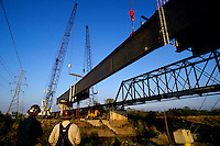Cranes lower a huge steel span into place at a bridge construction site.