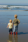 A 5 year old boy and 2 year old little sister looks out on the ocean from a beach on the Olympic Peninsula.