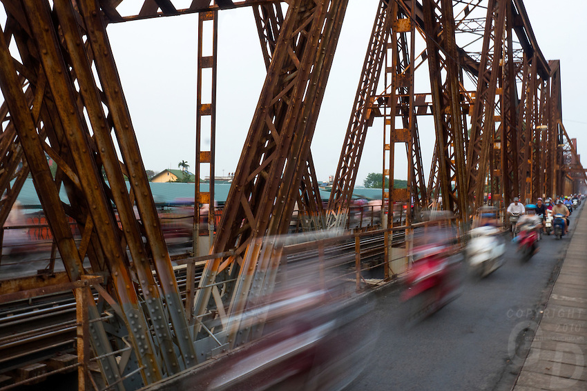 Long Bi&ecirc;n Bridge (Vietnamese: Cầu Long Bi&ecirc;n) is a historic cantilever bridge across the Red River that connects two districts, Hoan Kiem and Long Bien of the city of Hanoi, Vietnam. It was originally called Paul Doumer Bridge.<br /> <br /> The bridge was built in 1899-1902 by the architects Dayd&eacute; &amp; Pill&eacute; of Paris, and opened in 1903.Before North Vietnam's independence in 1954, it was called Paul-Doumer Bridge, named after Paul Doumer - The Governor-General of French Indochina and then French president. At 1.68 kilometres (1.04&nbsp;mi) in length, it was, at that time, one of the longest bridges in Asia. For the French colonial government, the construction was of strategic importance in securing control of northern Vietnam. From 1899 to 1902, more than 3,000 Vietnamese took part in the construction.<br /> It was heavily bombarded during Vietnam War due to its critical position (the only bridge at that time across the Red River connecting Hanoi to the main port of Haiphong). The first attack took place in 1967, and the center span of the bridge was felled by an attack by 20 USAF F-105 fighter-bombers. CIA reports noted that the severing of the bridge did not appear to have caused as much disruption as had been expected. The defence of Long Bien Bridge continues to play a large role in Hanoi&rsquo;s self-image and is often extolled in poetry and song. It was rendered unusable for a year when, in May 1972, it fell victim to one of the first co-ordinated attacks using laser-guided &quot;smart bombs&quot;.