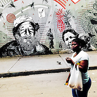 A Colombian woman passes in front of a graffiti stencil artwork, created by an artist named Dj Lu, in the center of Bogotá, Colombia, 13 March, 2016. A social environment full of violence and inequality (making the street art an authentic form of expression), with a surprisingly liberal approach to the street art from Bogotá authorities, have given a rise to one of the most exciting and unique urban art scenes in the world. While it's technically not illegal to scrawl on Bogotá's walls, artists may take their time and paint in broad daylight, covering the walls of Bogotá not only in territory tags and primitive scrawls but in large, elaborate artworks with strong artistic style and concept. Bogotá has become an open-air gallery of contemporary street art.