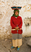 A Berber woman in Sefrou, Morocco, carries bread in a colourful basket on her head.