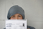 Foza Othman, a refugee from Aleppo, Syria, holds her family's United Nations-issued refugee registration documents in Amman, Jordan. Othman, who worked as a teacher in Syria but is not allowed to work in Jordan, has received support from International Orthodox Christian Charities, a member of the ACT Alliance. (Note: details on the document have been blurred to protect privacy.)
