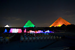 "Giza, Cairo, Egypt -- The three famous pyramids at Giza, surrounded by the ""queen's pyramids"" and with the remains of the funerary temple of Khafre (Khephren) (featuring the Great Sphinx) are spectacularly illuminated during the famous sound and light show at Giza. © Rick Collier / RickCollier.com."