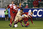 13 November 2009: Boston College's Karl Reddick (center) is challenged by NC State's Kris Byrd (9) and Farouk Bseiso (5). The North Carolina State University Wolfpack defeated the Boston College Eagles 1-0 at WakeMed Stadium in Cary, North Carolina in an Atlantic Coast Conference Men's Soccer Tournament Semifinal game.