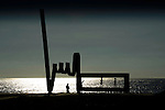 Silhouetted children playing  on a  sculpture next to the beach. Playa de las Americas with the background of Mount Teide. /Playa de las Americas, Tenerife, Canary Islands, Spain