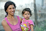 """THIS PHOTO IS AVAILABLE AS A PRINT OR FOR PERSONAL USE. CLICK ON """"ADD TO CART"""" TO SEE PRICING OPTIONS.   A woman holds her daughter in the largely Roma neighborhood of Gorno Ezerovo, part of the Bulgarian city of Burgas. Residents here don't self-identify much as Roma, because of the negative connotations associated with the word, so many refer to themselves as a Turkish-speaking minority."""