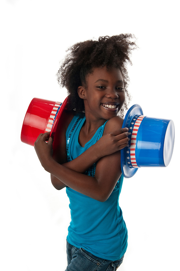 African American girl celebrates the 4th of July and plays with hats.