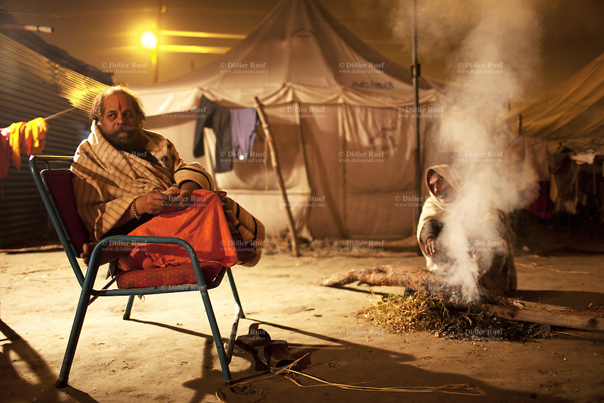 India. Uttar Pradesh state. Allahabad. Maha Kumbh Mela. A sanyasi is seated at night on a chair close some tents while an Indian Hindu devotee man is looking after the wood fire. The Kumbh Mela, believed to be the largest religious gathering is held every 12 years on the banks of the 'Sangam'- the confluence of the holy rivers Ganga, Yamuna and the mythical Saraswati. The Maha (great) Kumbh Mela, which comes after 12 Purna Kumbh Mela, or 144 years, is always held at Allahabad. Uttar Pradesh (abbreviated U.P.) is a state located in northern India. 18.02.13 © 2013 Didier Ruef