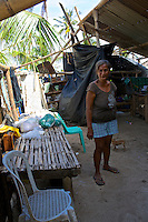 A Caluya local stand in her house that lost part of the roof during Typhoon Yolanda (Haiyan).