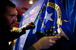 Audio-visual specialist Erik Lund steams a Nevada state flag before GOP presidential candidate Newt Gingrich arrives at a campaign event at Great Basin Brewing Company in Reno, Nevada, February 1, 2012.