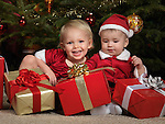 Two year old girl and an eight month old boy sitting with presents under a Christmas tree