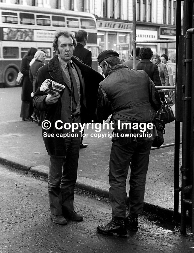 Soldiers on security duty in the run-up to Christmas 1972 routinely search shoppers, workers, etc, visiting the city centre in Belfast, N Ireland, December 1972. Generally it is endured with a mixture of stoicism and indifference, 197212070766a<br /> <br /> Copyright Image from Victor Patterson, 54 Dorchester Park, Belfast, UK, BT9 6RJ<br /> <br /> t1: +44 28 9066 1296 (from Rep of Ireland 048 9066 1296)<br /> t2: +44 28 9002 2446 (from Rep of Ireland 048 9002 2446)<br /> m: +44 7802 353836<br /> <br /> e1: victorpatterson@me.com<br /> e2: victorpatterson@gmail.com<br /> <br /> The use of my copyright images is subject to my Terms &amp; Conditions.<br /> <br /> It is IMPORTANT that you familiarise yourself with them. They are available on my website at www.victorpatterson.com.<br /> <br /> None of my copyright images may be used on a website unless they are visibly watermarked, i.e. &copy; Victor Patterson within the body of the visible image. Metadata denoting my copyright must NOT be deleted. <br /> <br /> Web use is extra at currently recommended NUJ rates.