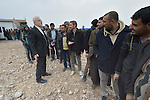 Father Emanuel Youkhana, a priest of the Holy Apostolic Catholic Assyrian Church of the East, talks with men lined up at a processing center for displaced families outside Mosul, Iraq, on January 27, 2017. The men's families wait out of sight while the men complete the paperwork. <br /> <br /> Although the eastern portion of the city has been liberated from ISIS, fierce fighting is predicted as the army moves to retake the remainder of the city.