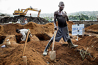 A grave digger at the King Tom cemetery helping excavate a group of pre-dug graves. Beside him a notice marks the details of the person buried there. Due to the rapid increase in burials, caused by the ebola crisis, the cemetery is being enlarged and parts of a nearby rubbish dump is also being used to bury the dead.