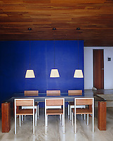 The blue wall in this contemporary dining room makes a bold statement