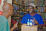 "A wholesaler in Conakry, Guinea tells a customer about ""Sur'Eau,"" a chlorine product that makes water safe to drink.  Sur'Eau is distributed by the international social marketing organization, Population Services International."
