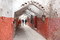 A narrow street with overhead trusses and red painted walls in the Mellah or new Jewish quarter, which has a central street with parallel lanes running off it, built by the decree of Sultan Moulay Sliman on 5th August 1807, in the East of Tetouan, on the slopes of Jbel Dersa in the Rif Mountains of Northern Morocco. The original Jewish quarter was destroyed in 1790 by Sultan Moulay Yazid and the Jewish population of Tetouan is exclusively of Spanish origin, arriving first after the expulsions in the 15th century. Picture by Manuel Cohen