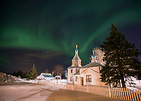 The aurora borealis glow in the sky above the Holy Assumption of the Virgin Mary Russian Orthodox Church in Kenai, Alaska. The bright green display of the northern lights at times filled the sky with green light.
