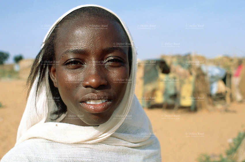 Sudan. West Darfur. Ryiadh. Ryiadh is located on the outskirts of the town of Al Geneina and is a camp for internally displaced people (IDP)) from the civil war. A young beautiful woman, wearing a white veil on her head, stands near her poor living wood hut. © 2004 Didier Ruef
