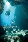 Paradise Reef, Taveuni, Fiji; a scuba diver swims through sun rays streaming through the shallow water at the opening to an underwater cavern created lava tubes, model released