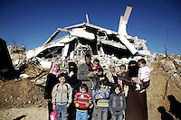 Esbet Abed Rabbo, Gaza, Palestine 20090205 -  From back row left: Sabrin (14), Hoda (16), dad Ahmad (39) with Hanin, Amna (18) with Ahmad (1 year and 5 months). Horia (34) with Rawan (9 months). Front left: Hamad (10), Ali (5), Ghada (6) og Ghadir (6) in front of their ruined house in the temporary tent camp in Esbet Abed Rabbo, Gaza. Photo/copyright: Torbjorn Gronning