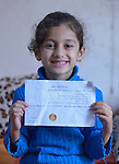 Rahaf Saeed Seno, a 6-year old Yazidi girl displaced from Bashiqa, Iraq, by the Islamic State group in 2014, holds a school report in her family's temporary home in Dohuk. Her father participates in a skills training program sponsored by the Christian Aid Program Nohadra - Iraq (CAPNI).