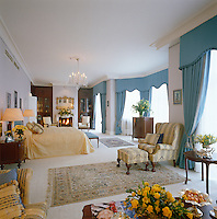 This spacious bedroom has been decorated in a traditional style in a combination of blue and gold