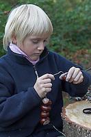 Kinder basteln mit Kastanien, Junge fädelt Kastanie auf einen Draht auf
