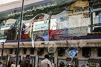 A mural, seen through a glass window, on Enqelab Avenue featuring supreme leader of Iran Ali Khamenei (right), a soldier (Hossein Fahmideh) and the spiritual leader of the Iranian revolution Ayatollah Khomeini (left).