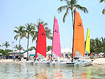 Three catamarans with brightly colored sails sit on the beach of Founders Park Beach, Islamorada, Florida; people gather along the shore