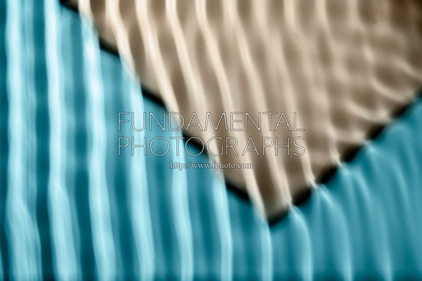 REFRACTING WAVES IN RIPPLE TANK.Waves refracting off shoal in ripple tank..When vertical plane waves encounter shoal, the angle of the wave changes due to the altered depth of the water. The wave bends around the shoal due to resistance.