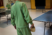 Elderly prisoners playing table tennis for exercise in an indoor recreational room, watched over by guards, in Onomichi prison, Japan.  Monday, May 19th 2008.