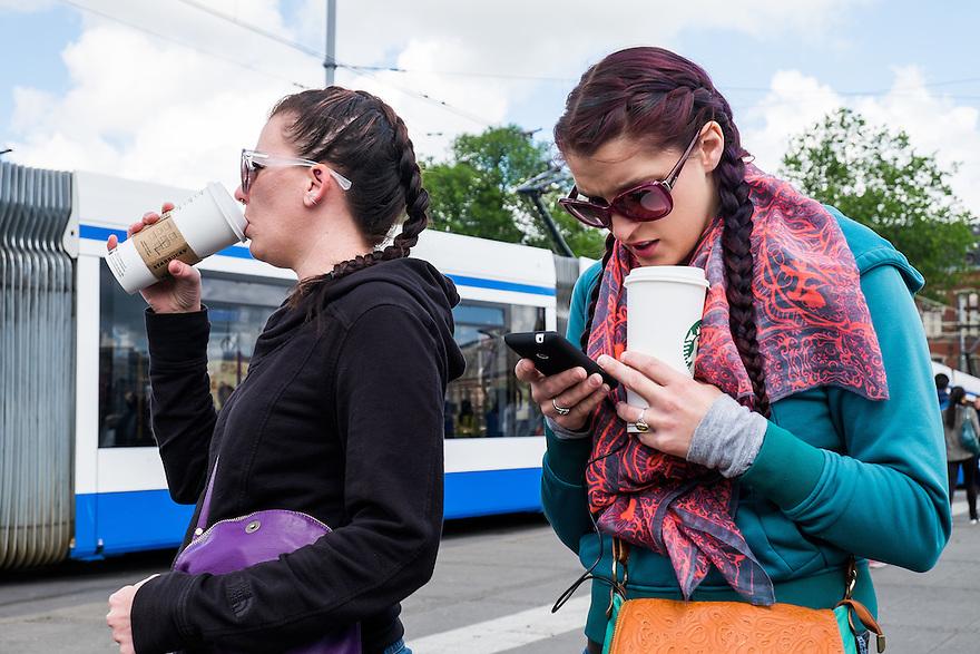Nederland, Amsterdam, 30 mei 2015<br /> NS station Amsterdam Centraal met reizigers die net uit het station zijn gekomen. Touristen kijken op hun smartphone waar ze naar toe moeten. <br /> Foto: Michiel Wijnbergh