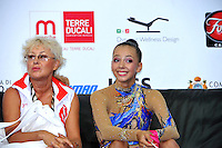 """(L-R) Coach and Daria Dmitrieva of Russia smiles at """"kiss & cry"""" at 2010 Pesaro World Cup on August 27, 2010 at Pesaro, Italy.  Photo by Tom Theobald."""