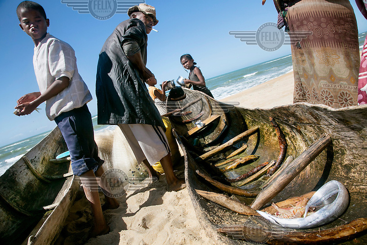 Children help a fisherman after he returns with a meagre catch after spending half the night with his nets and canoes on the Indian Ocean.