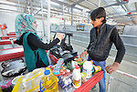 Mohammed Nayef pays for groceries in a supermarket inside the Zaatari refugee camp near Mafraq, Jordan. Nayef, who fled his home war-torn Daraa, Syria, in 2013, receives a monthly food allowance from the United Nations High Commissioner for Refugees, issued to him on an electronic debit card. He can then shop for the food he wants and pay with the debit card. Aid workers say the process affords more dignity and freedom of choice to refugee families than lining up at warehouses to receive food rations.<br /> <br /> Established in 2012 as Syrian refugees poured across the border, the camp held more than 80,000 refugees by 2015, and was rapidly evolving into a permanent settlement. The ACT Alliance provides a variety of services to refugees living in the camp.