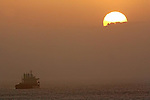 A large fishing vessel sails into the San Francisco Bay during sunrise, California.