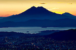 Sunrise behind San Vincente Volcano, rising over Lake Ilopango and the city lights of San Salvador, El Salvador.