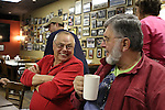 "Mitch Wilson, left, and Gary ""Tub"" Whitaker reminisce over coffee as Judd Weaver (back left) rolls the chili containers back to the kitchen. Photo by Alex Holt"