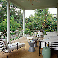 The large second floor porch benefits from tree-top views and features seagrass flooring and wrought iron seating dressed with white cushions