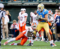 SAN FRANCISCO, CA - December 31, 2011: UCLA tight end Joseph Fauria (8) attempts to break the tackle by University of Illinois linebacker Ashante Williams (25) at AT&T Park in San Francisco, California. Final score Illinois wins 20-14.