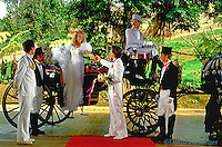 Cinderella wedding, bride getting out of horse drawn carriage, groom helping coachmen