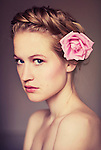 Close portrait of young woman with braided hair and pink flower