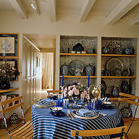 A blue and white theme is repeated throughout this dining room, from the laid table to the the collection of crockery on display